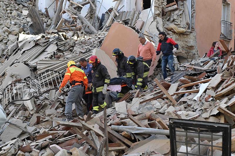 Сотрудники спасательных служб извлекают из-под завалов людей, пострадавших в результате землетрясения в Италии