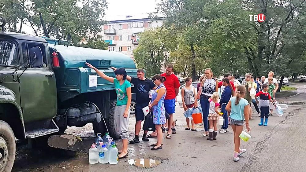 Жители в очереди за питьевой водой