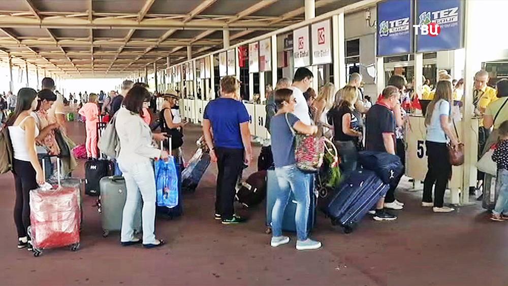 Пассажиры в очереди на стойках регистрации в аэропорту