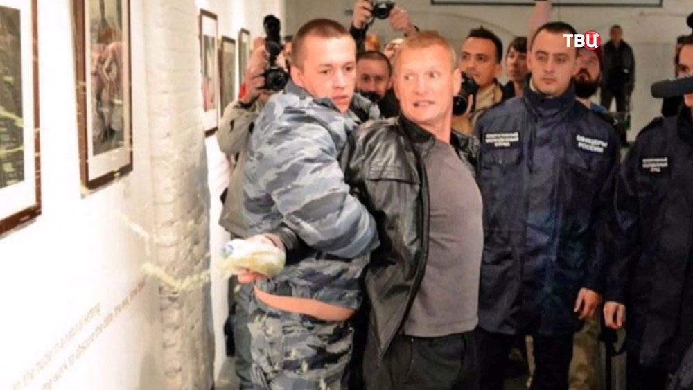 Охрана задерживает мужчину на выставке Стерджесса
