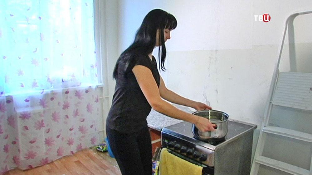Женщина греет воду на плите