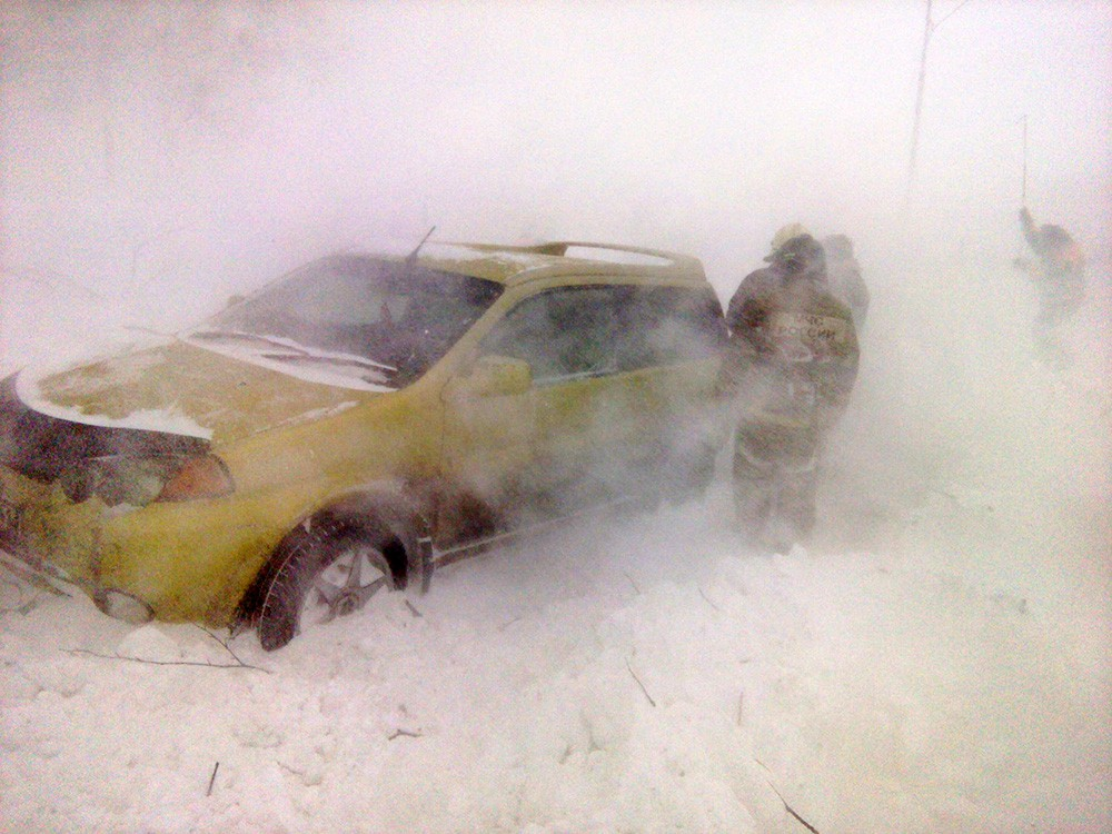 Спасатели МЧС работают во время снежного бурана на трассе