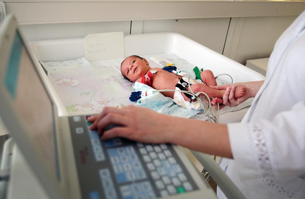 Врачи обследуют новорожденного ребенка
