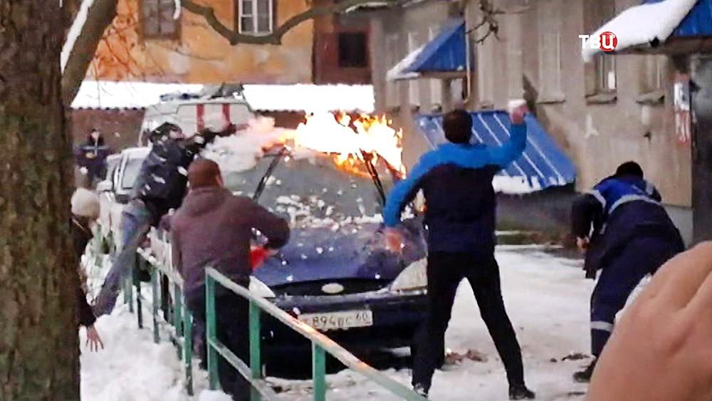 Люди тушат горящую машину