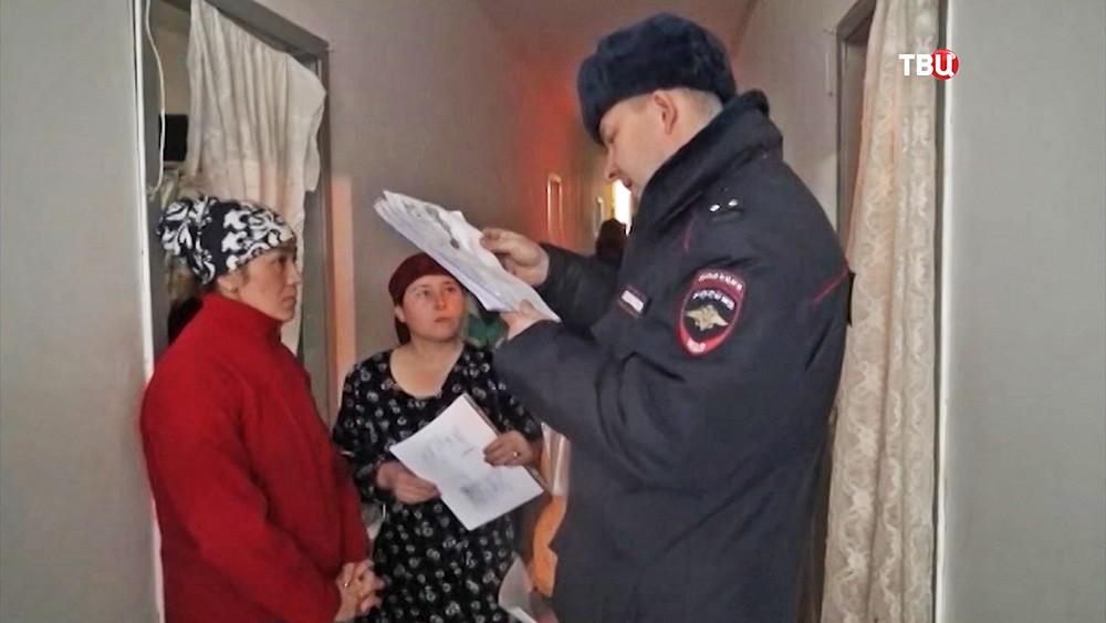 Сотрудник полиции проверяет документы у мигрантов