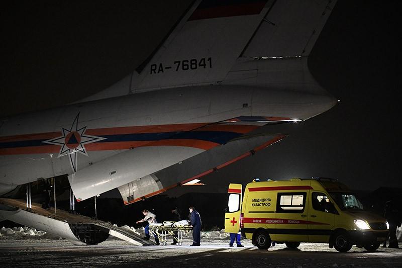 Сотрудники медицинской службы выгружают из самолета МЧС России детей