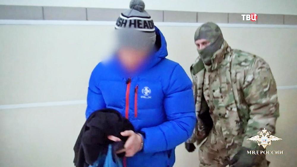 Задержанный участник хакерской группы под конвоем