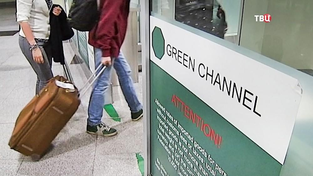 """Пассажиры проходят по """"зеленому коридору"""" в зоне таможенного досмотра"""