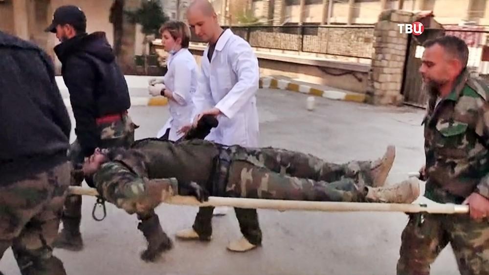 Врачи эвакуируют пострадавшего в боевых действиях в Сирии