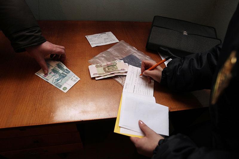 Сотрудница Федеральной службы судебных приставов выписывает квитанцию на оплату
