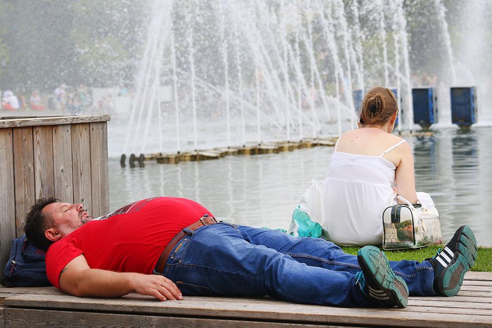 Мужчина отдыхает у фонтана