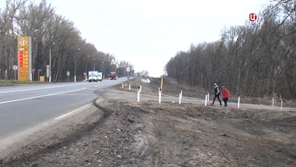 Школьники идут вдоль шоссе