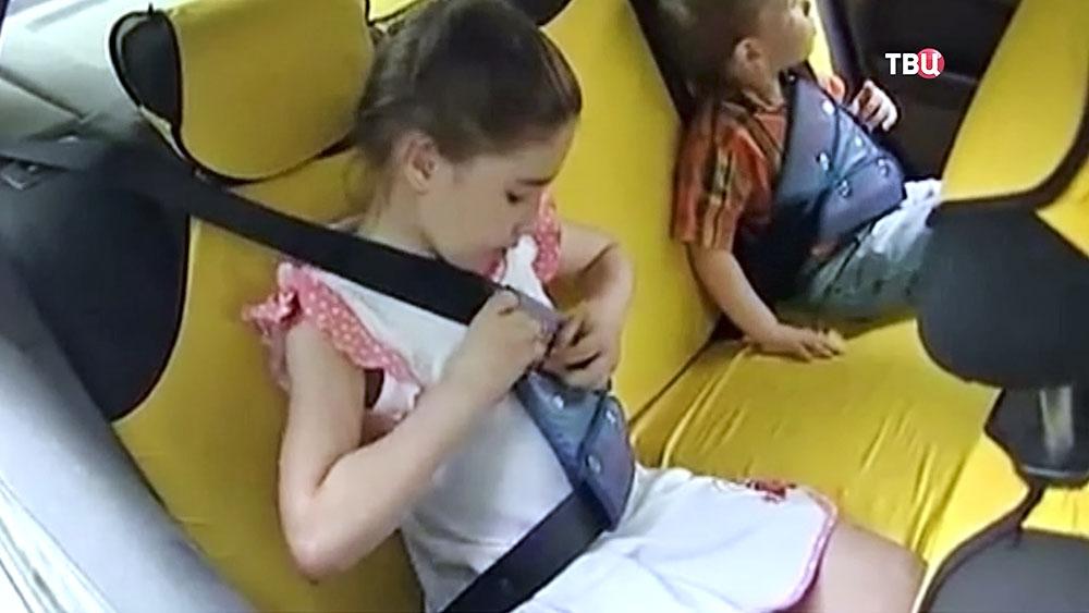 Дети пристегиваются в машине