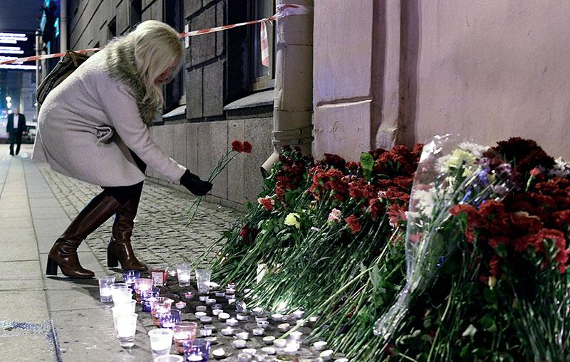 """Женщина возлагает цветы рядом со станцией метро """"Технологический институт"""""""