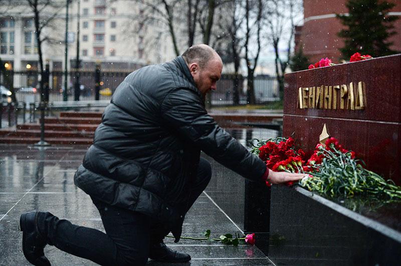 Мужчина возлагает цветы к мемориалу города Ленинград