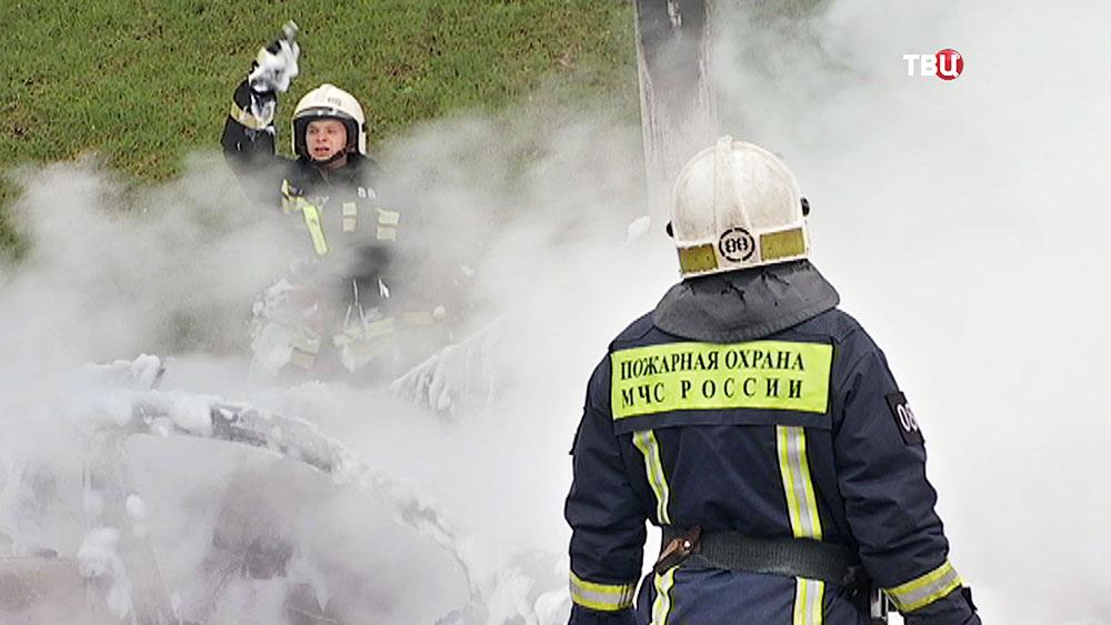 Пожарные тушат горящий автомобиль
