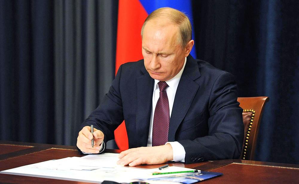 Президент России Владимир Путин подписвает документ