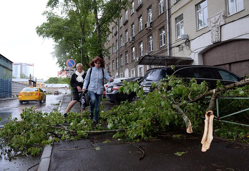 Прохожие перешагивают поваленные ураганом деревья в Москве