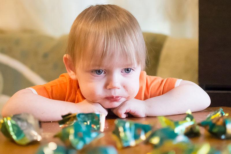 Мальчик ест конфеты