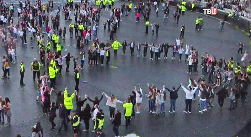 Полицейские Великобритании пляшет вместе со зрителями на концерте
