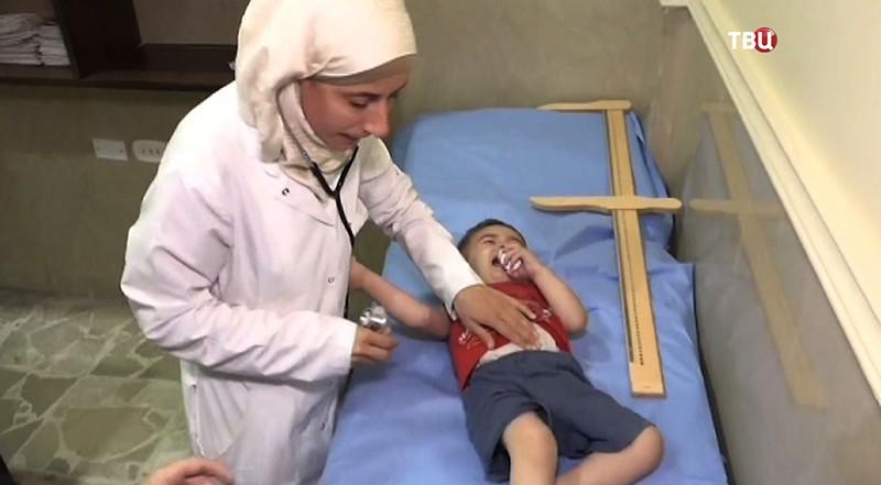 Сирийские медики осматривают ребенка
