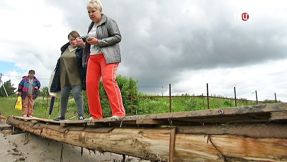 Жители поселка переходят реку по временному мосту