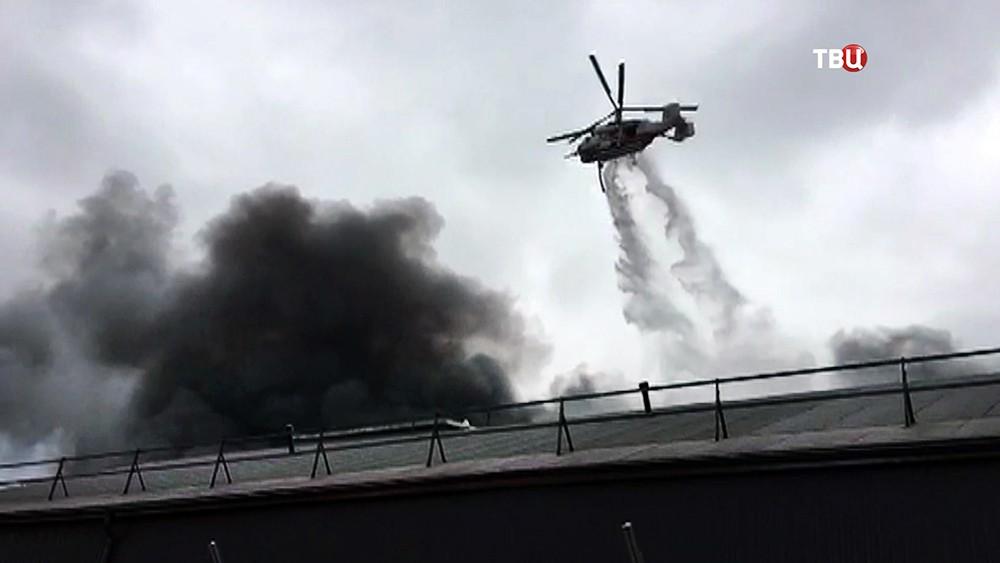 Пожарный вертолет сбрасывает воду на место возгорания в промзоне