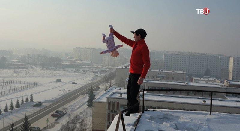 Блоггер держит ребенка на крыше вниз головой