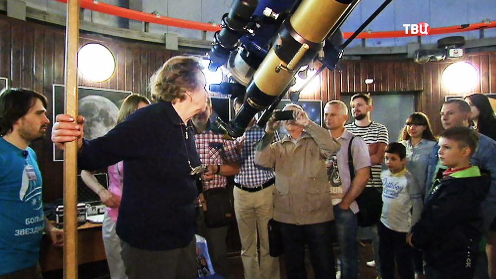 Посетители обсерватории смотрят в телескоп