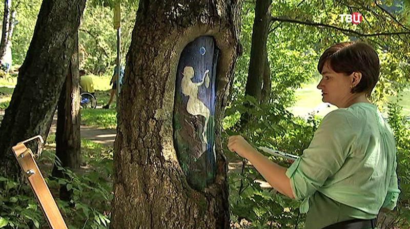 Художник расписывает деревья