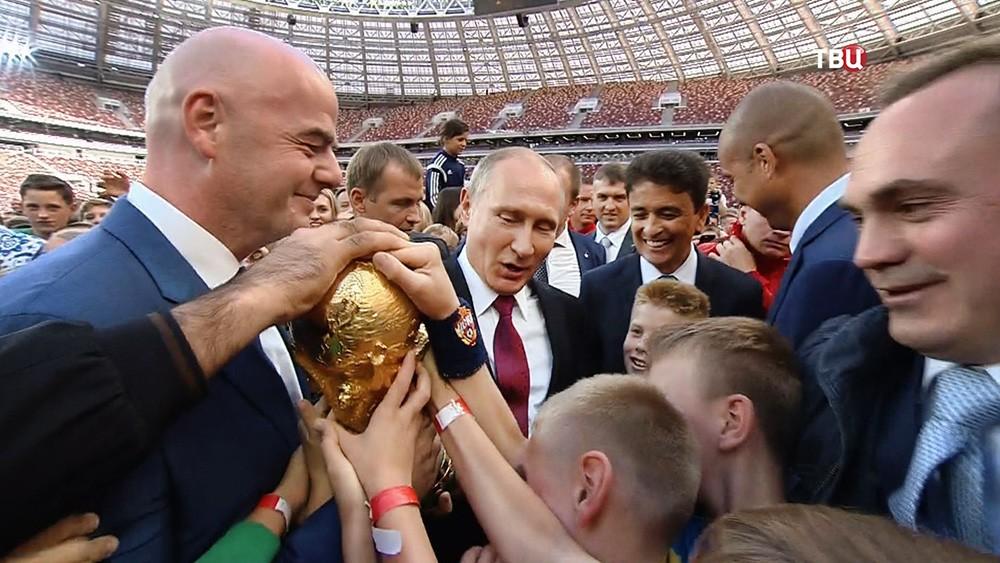 Владимир Путин и Джанни Инфантино с кубком ЧМ по футболу 2018 года