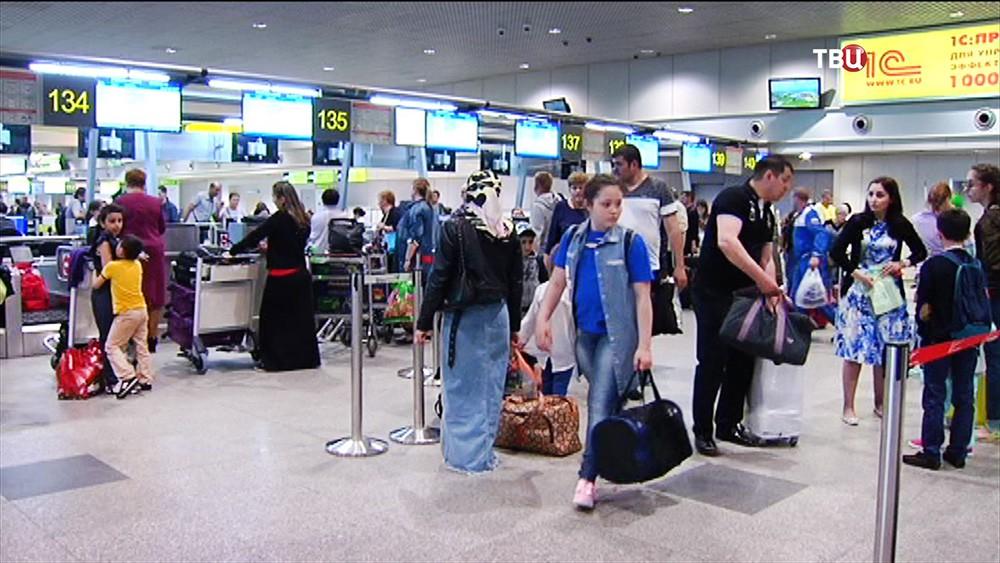 Пассажиры на стойке регистрации в аэропорту