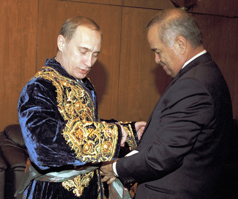 Владимир Путин примеряет национальный узбекский халат