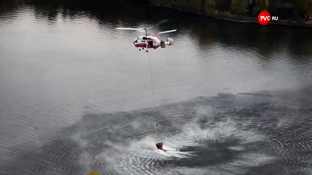 Пожарный вертолет набирает забор воды