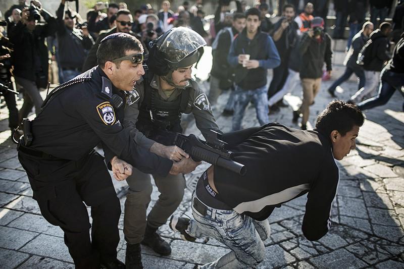 Израильские полицейские задерживают палестинского манифестанта