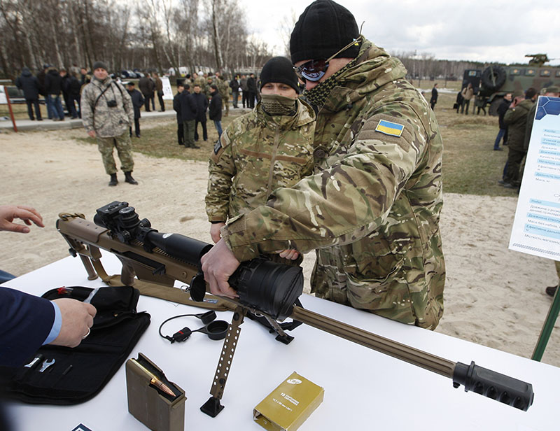 Украинский военный осматривает снайперскую винтовку