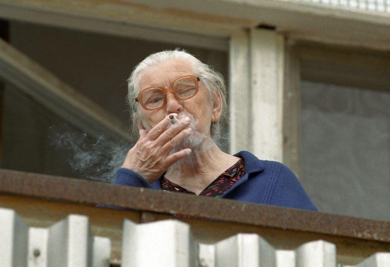 Престарелая женщина курит на балконе