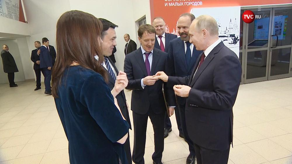 Владимир Путин во время осмотра выставки в рамках форума малых городов и исторических поселений