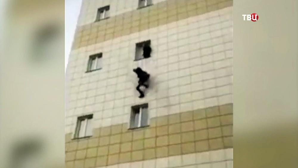 """Люди спасаются от пожара в торговом центре """"Зимняя вишня"""" в Кемерово"""