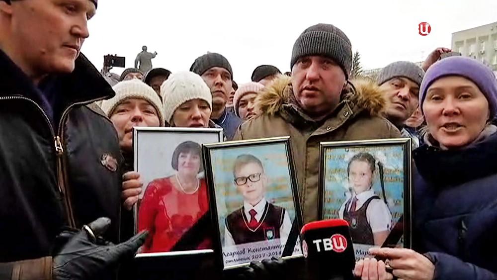 Жители Кемерова держат фотографии детей погибших в пожаре в торговом центре