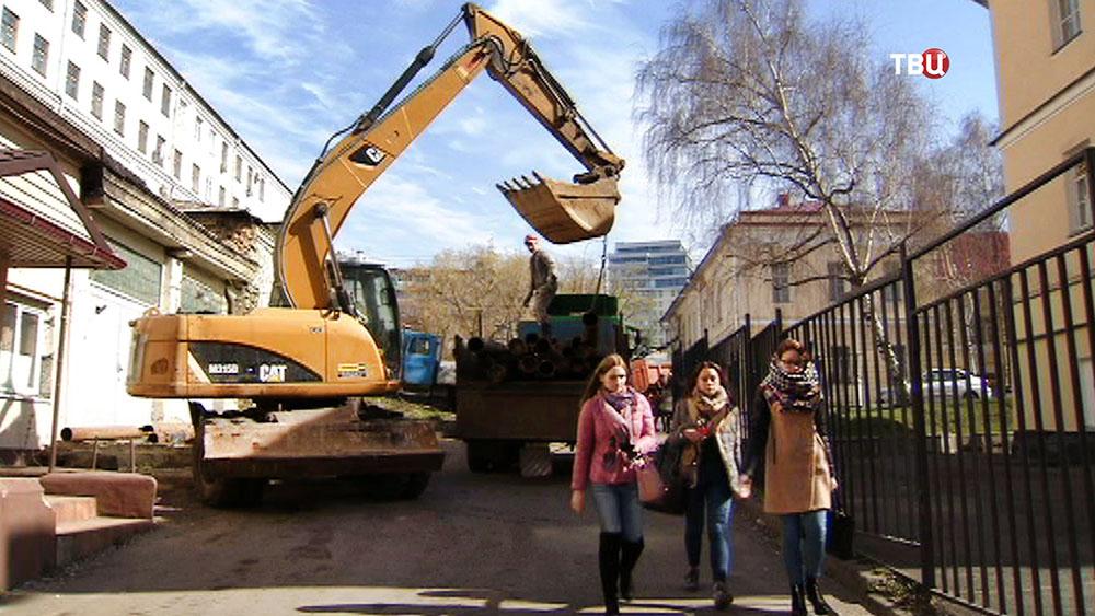 Экскаватор выполняет строительные работы