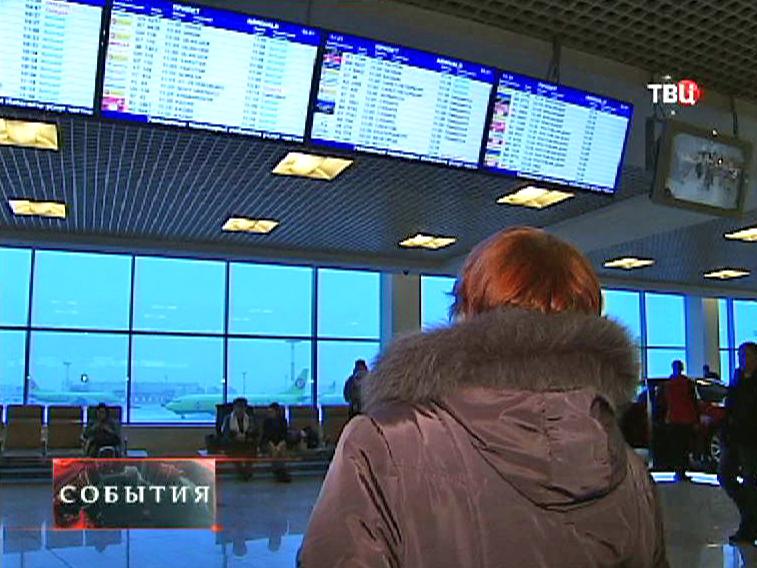 Женщина смотрит расписание авиарейсов на табло