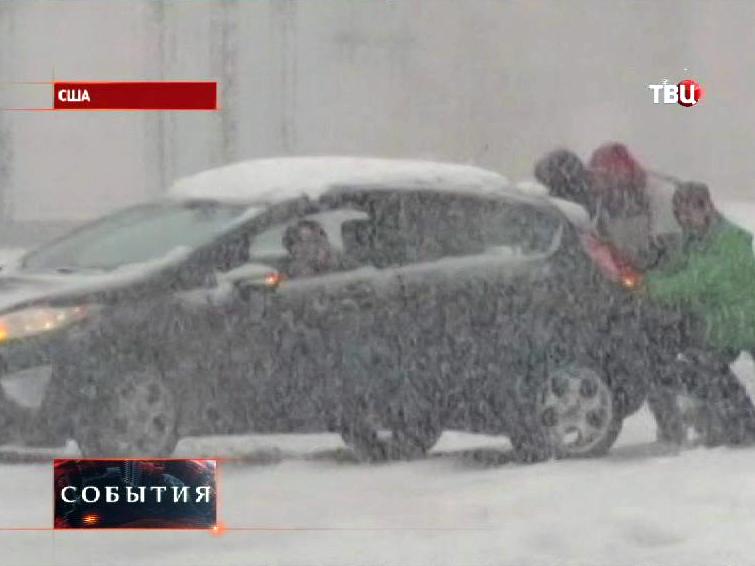 Жители США выталкивают машину из сугроба