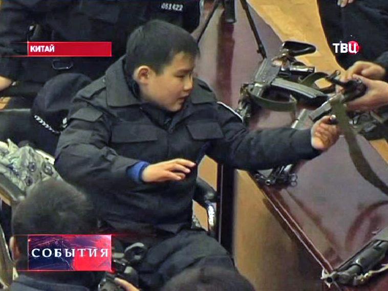 Китайский мальчик-инвалид осматривае оружие полиции