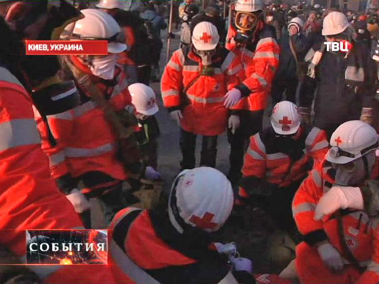 Медики выносят пострадавших в столкновениях сторонников оппозиции с Украинской милицией