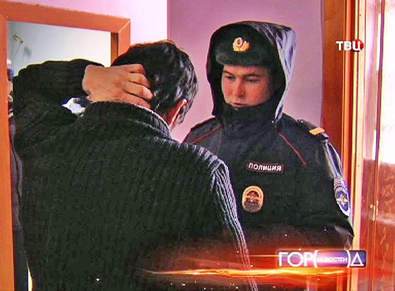 Сотрудник полиции проверяет документы у мигранта