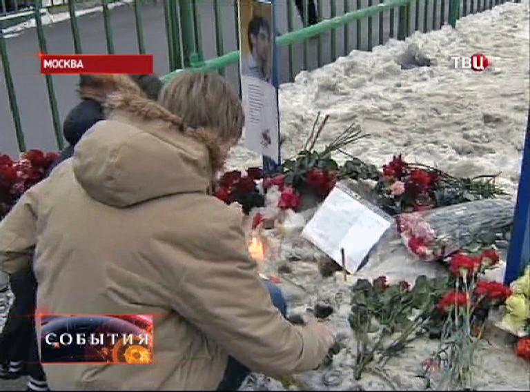 Люди приносят цветы к школе в Отрадном