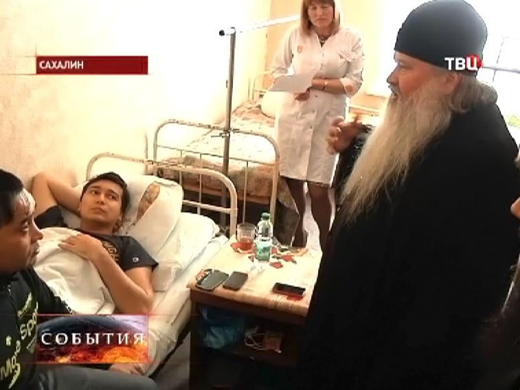 Священник навещает пострадавшего в больнице