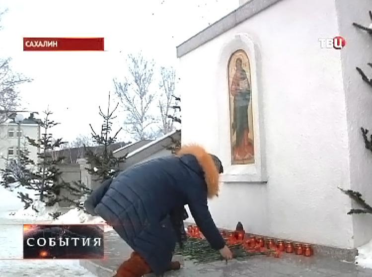 Люди приносят цветы и свечки к храму