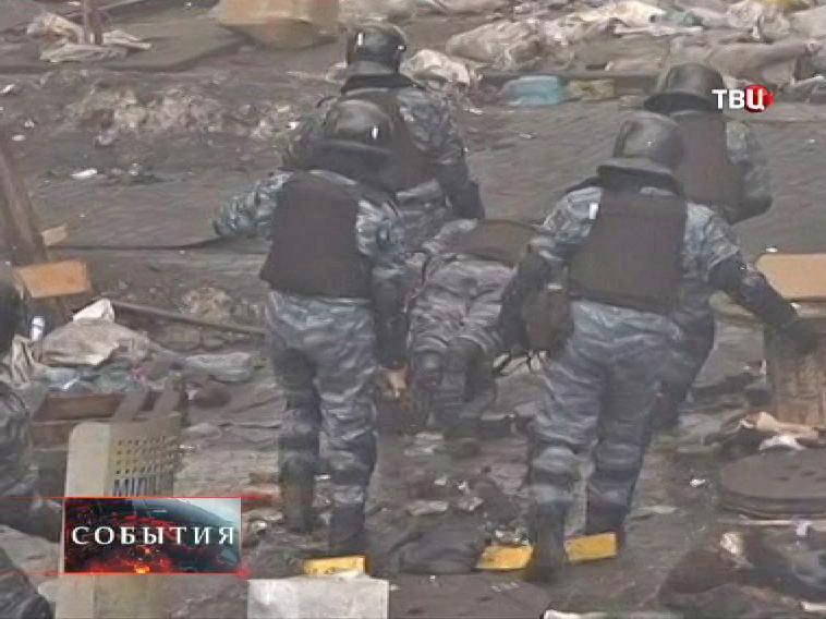 Милиционеры выносят своего раненого сотрудника во время беспорядка в Киеве